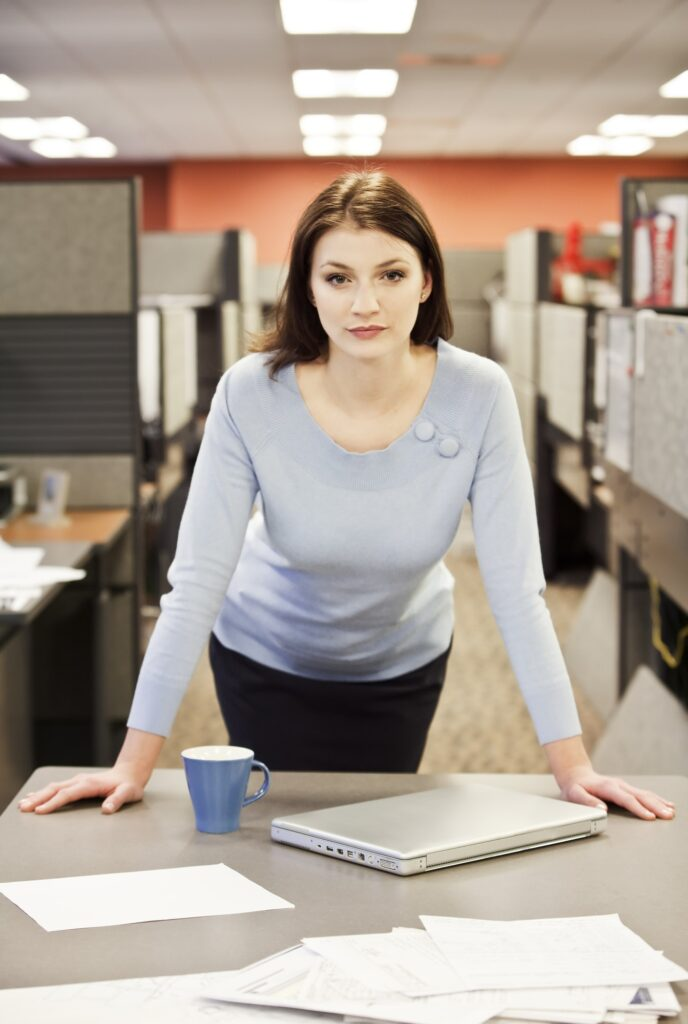 A portrait of a young business woman in her cubicle in a corporate office.