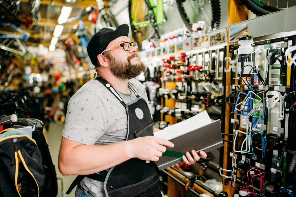 Bicycle mechanic with notebook in bike shop