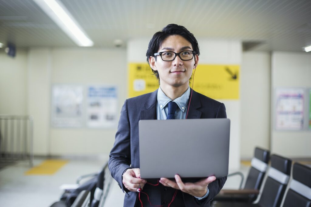 Businessman wearing suit and glasses standing at train station, holding laptop.