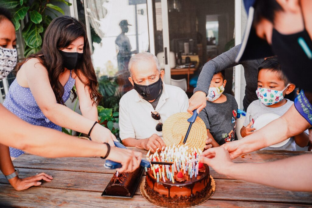 Diverse family celebrating birthday active baby boomer senior wearing masks at home.