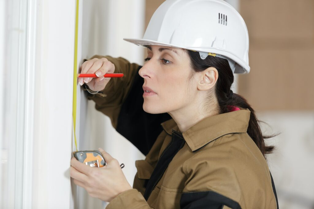 female builder measuring a wall