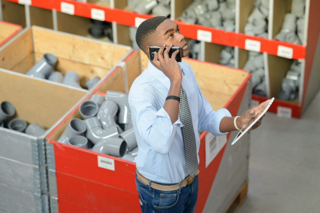 Man in pipe fittings department, holding tablet and speaking on telephone