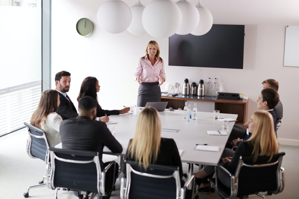 Mature Businesswoman Addressing Group Meeting Around Table At Graduate Recruitment Assessment Day