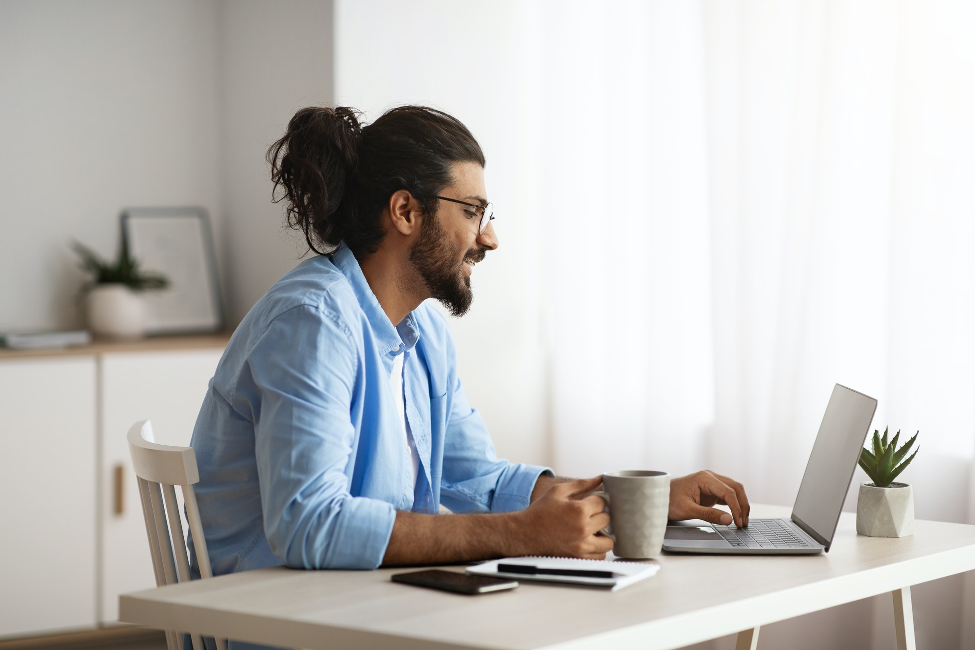 Remote Work. Male Freelancer Using Laptop And Drinking Coffee At Home Office